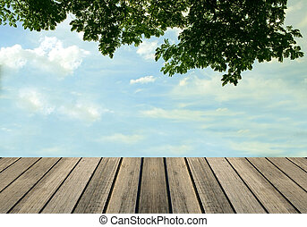 wooden floor with green leaves and sky background