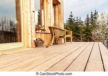 Wooden floor, Wooden terrace at an ecological house. Wicker chairs on a wooden terrace by the forest.
