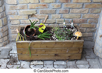 Wooden flower pot with plants beside wall