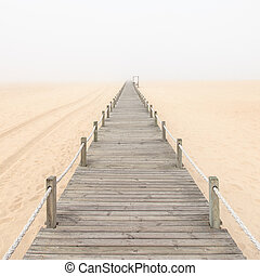 Wooden footbridge on a foggy sand beach. Figueira da Foz, Portugal, Europe.