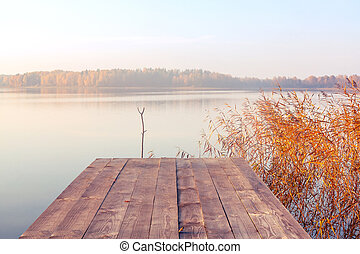 Wooden footbridge on the lake at sunrise on a foggy morning