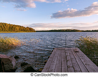 Wooden footbridge on the lake on a summer day at sunset