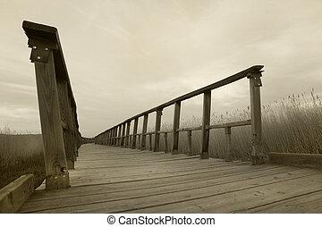 Wooden footbridge walkway. Sepia tone. Tablas de Daimiel. Ciudad Real. Spain.