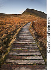 Wooden footpath over marshland leading to Pen-y-Ghent in Yorkshire Dales National Park