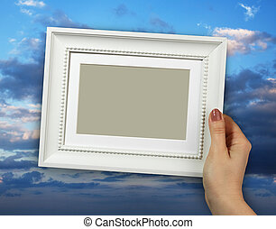 Wooden frame in woman hands on the background blue sky