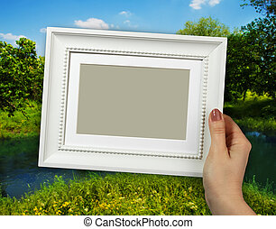 Wooden frame in woman hands on the forest background