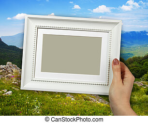 Wooden frame in woman hands on the Mountain background