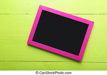Wooden frame on green wooden background