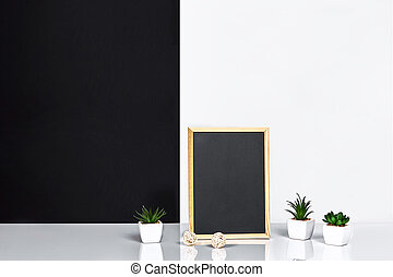 Wooden frame with black place for text. Mock up. Stylish room interior. Green plant in a white pot on black-white wall background