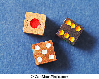 wooden gambling dices on blue cloth closeup