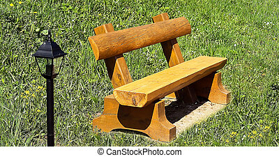 Wooden garden bench on a lawn with a lantern