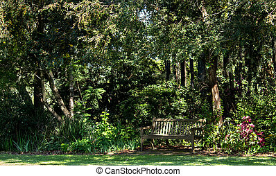 Wooden garden seat bench set in the shade of a large tree with many shrubs and green grass lawn in dappled sunlight