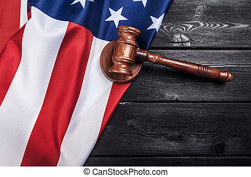 Wooden gavel and USA flag on table close up
