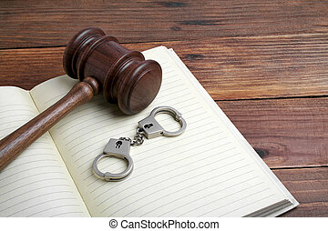 Wooden gavel, open book and handcuffs on wooden background