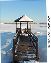 Wooden gazebo by the river at winter.