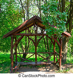 Wooden gazebo in the forest.