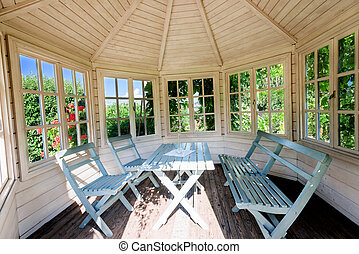 Wooden gazebo inside at sunset on summer evening