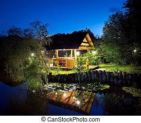 Wooden gazebo lit lanterns on the lake