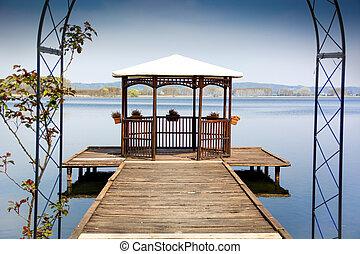 Wooden gazebo on dock over peaceful lake