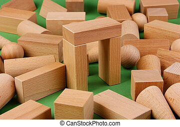 wooden geometric shapes on a green