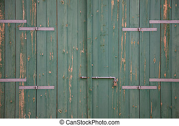 Wooden green aged door, rusty latch and padlock. Close up, details