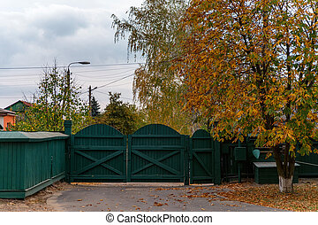 Wooden green fence in countryside in autumn at cloudy day