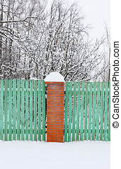 wooden green fence with brick pillar