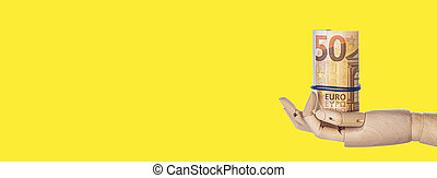 Wooden hand with money isolated on yellow background.