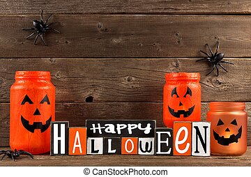 Wooden Happy Halloween sign with mason jar Jack o Lanterns against a rustic old wood background