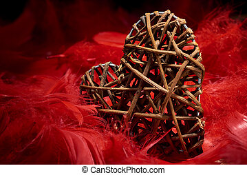 wooden heart in red feathers - wooden heart in the midst of ...