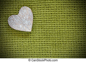 Wooden heart on a green fabric background with vignette