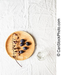 Wooden homemade round plate with plums and dry branch with leaves on white cloth background. Top view. Copy space