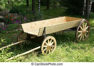 Wooden horse cart on green field in garden