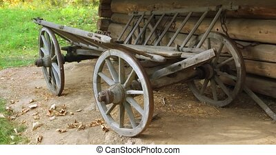 Old fashioned, wooden horse cart for cargo is chained to the wall of a log cabin on a rural farm in Ukraine. 4k DCI stock footage