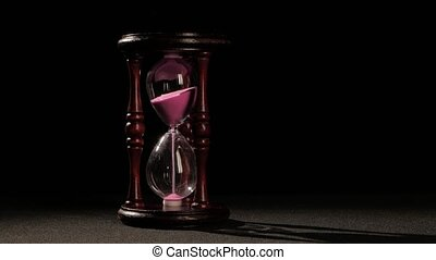 Wooden hourglass. Jet of sand in the hourglass. Black