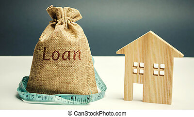 Wooden house and a bag with the word Loan and a tape measure. Buying a home in debt. Family investment in real estate and risk management concept. Loan for a mortgage. Lack of money for debt repayment