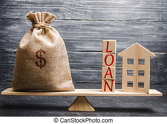 Wooden house and a bag with the word Loan on the scales. Buying a home in debt. Loan for a mortgage. Successful debt repayment. Family investment in real estate and risk management concept