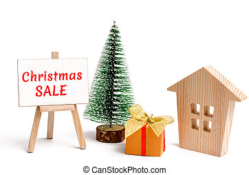 Wooden house and Christmas tree with the inscription Christmas Sale. Christmas Sale of Real Estate. New Year discounts for buying house. Purchase apartments at a low price. Winter resort and vacation