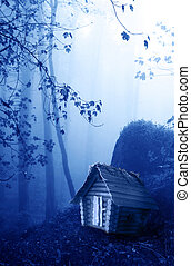 Wooden house and mysterious landscape of foggy forest