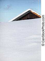 Wooden house covered in snow