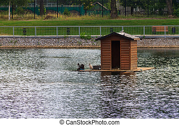 Wooden house for swans on a lake in city park