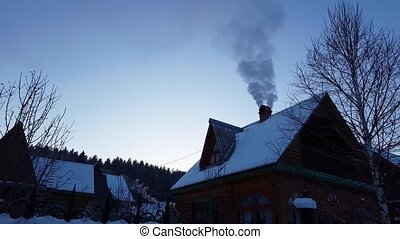 wooden house in the mountains. smoke from chimney action in...