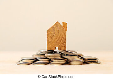 Wooden house model on a pile of coins.