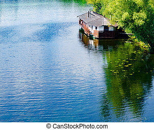 Wooden house on the river. Summer.