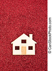 Wooden house shape on red glitter background