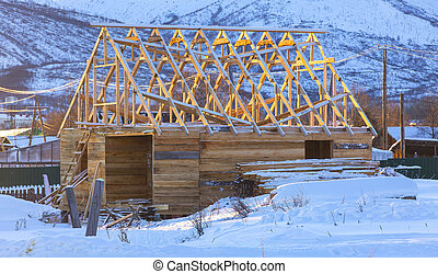 wooden house under construction in winter