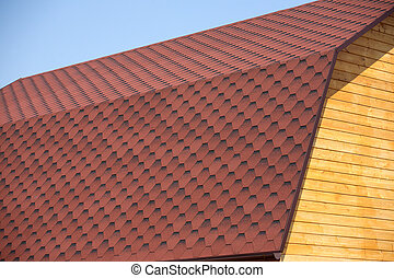 Wooden house wall and brown roof ti