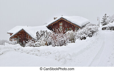 wooden houses covered with snow  in alpine mountain village under snowfall