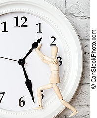 Wooden human figure trying to stop the arrow of the clock. Deadline concept