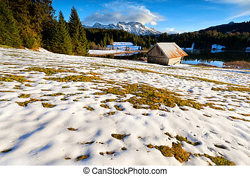 wooden hut on smow alpine meadow by lake